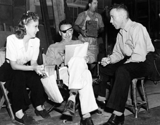 Ida Lupino smiling, with Raoul Walsh and Humphrey Bogart behind the scenes of High Sierra